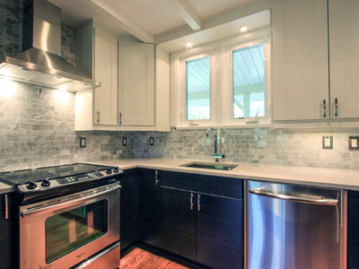 modern kitchen renovated with black and white cabinets and marble backsplash